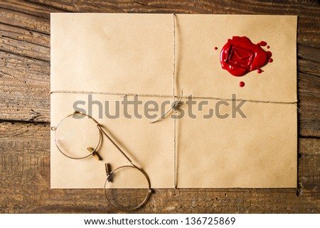 Envelope with imprinted sealing wax and old glasses - stock photo