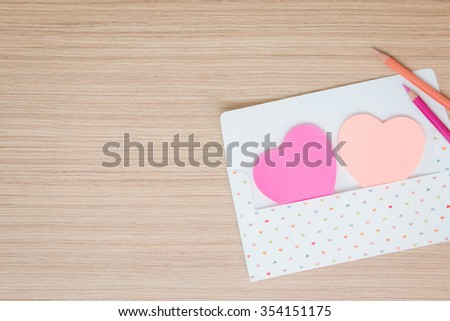 Envelope with paper note heart or post it for valentine day on wooden table background - stock photo