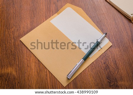 Envelope with pen and white paper
