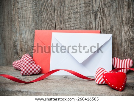 Envelope with red hearts for valentine day on wooden background - stock photo
