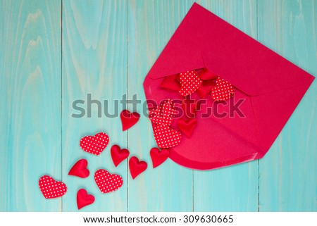 Envelope with red hearts on the blue wooden background