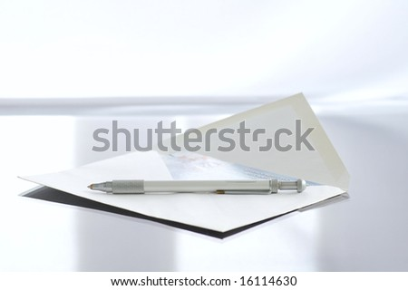 Envelope with the letter on the writing desk against the bright background - stock photo