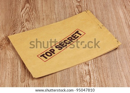 Envelope with top secret stamp on wooden background - stock photo