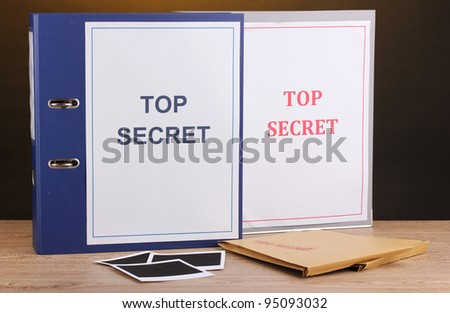Envelopes and folders with top secret stamp and photo papers on wooden table on brown background - stock photo