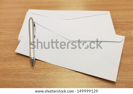 envelopes with a pen on a wooden table - stock photo