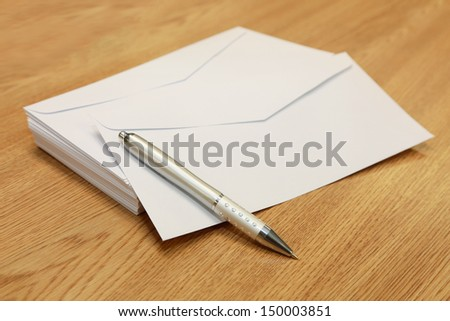 envelopes with a pen on a wooden table