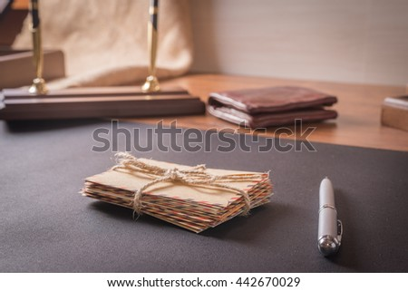 Envelopes with pen on a leather table