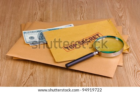 Envelopes with top secret stamp with magnifying glass and money on wooden background - stock photo