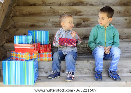 envious child. elder brother is jealous of a pile of gifts that are gifted to younger brother - stock photo