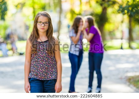 Envious girls discriminating her girlfriend by talking behind her - stock photo