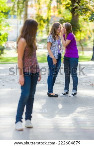 Envious girls talking behind her girlfriend in park - stock photo