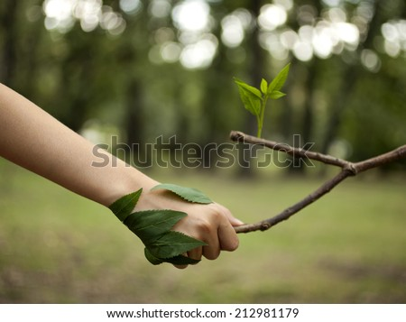 Environment concept. Handshake between human hand and tree. - stock photo