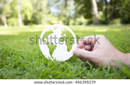 Environment concept, paper globe on the grass with hands, blur