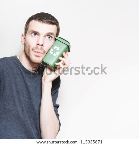 Environment Conscience Man Thinking With Mini Green Wheelie Bin In A Depiction Of Refuse Recycling Ideas - stock photo