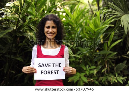 environment conservation: woman holding a save the forest  sign smiling