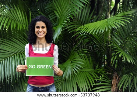 environment conservation: woman in the forest holding a go green  sign smiling - stock photo