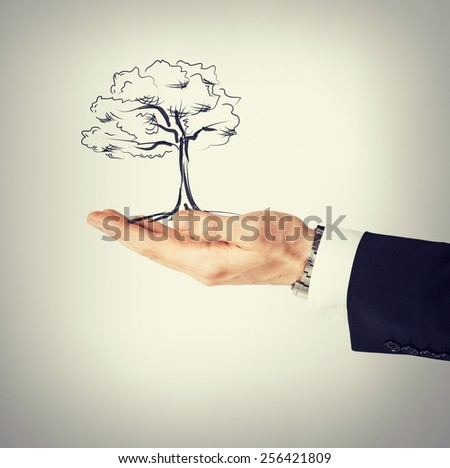 environment, ecology and nature protection concept - man with small tree in his hand - stock photo
