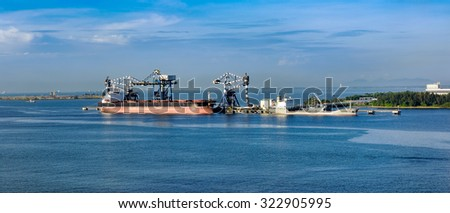 Environment-friendly continuous ship unloader at coal-fired power plant work with cargo ships at waterfront in Johor, Malaysia. - stock photo