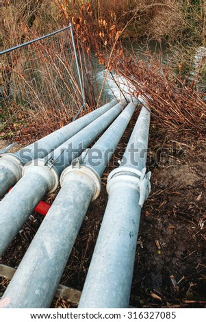 Environment problem - culvert spewing polluted water from factory into clean river - stock photo