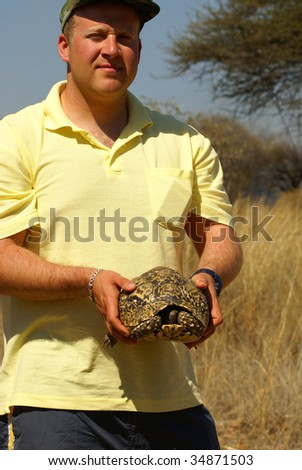 Environment protection volunteer holding a tortoise - stock photo