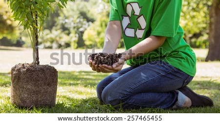 Environmental activist about to plant tree on a sunny day - stock photo