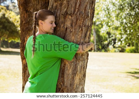 Environmental activist hugging a tree in the park on a sunny day - stock photo