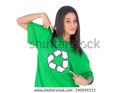 Environmental activist pointing to the symbol on her tshirt and smiling on white background - stock photo