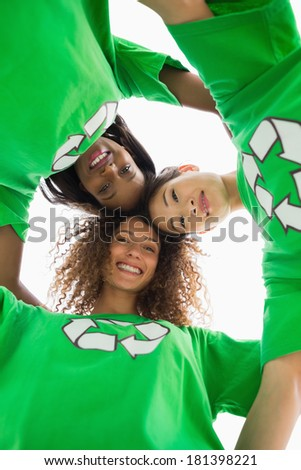 Environmental activists hugging and looking down at camera on white background - stock photo