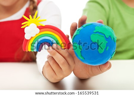 Environmental awareness and education concept - child hands holding earth globe and rainbow made of clay - stock photo
