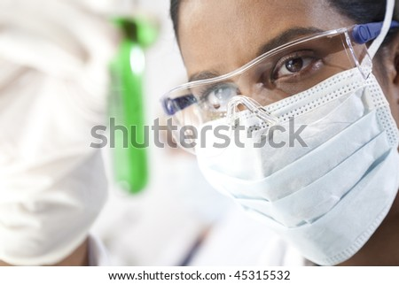 Environmental concept shot of a female Asian medical or scientific researcher or doctor looking at a test tube of a green solution in a laboratory. - stock photo