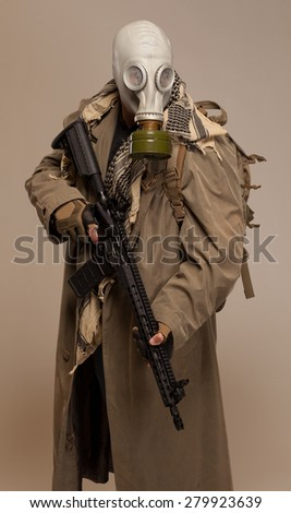 Environmental disaster. Post apocalyptic survivor in gas mask looking at camera. - stock photo