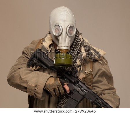 Environmental disaster. Post apocalyptic survivor in gas mask with rifle looking at camera. - stock photo