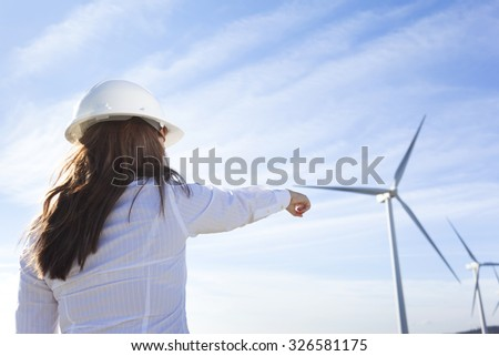 Environmental engineer pointing to windmill at wind farm