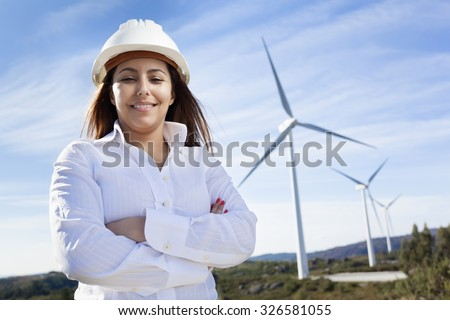 Environmental engineer standing with arms crossed at wind farm - stock photo
