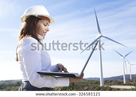 Environmental engineer with a laptop at wind farm - stock photo