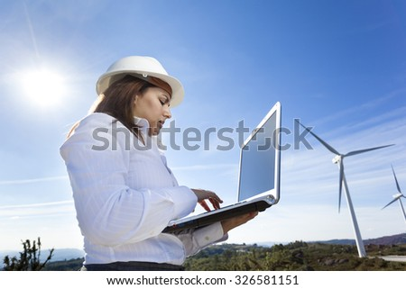 Environmental engineer with a laptop at wind farm