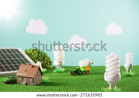 Environmental friendly toy town with model house, CFL lamps as trees and tractor carrying a light bulb - stock photo