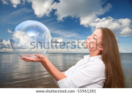 Environmental picture of young beautiful girl with globe against the blue sky and sea - stock photo