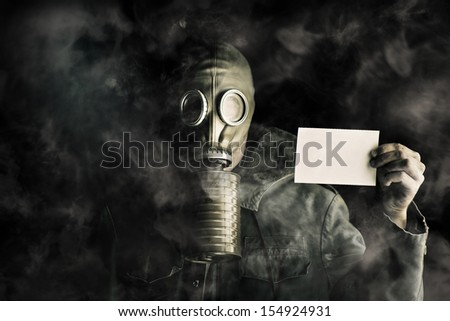 Environmental pollution concept with a man wearing a gas mask in a smoky polluted atmosphere holding up a blank ID card to identify himself under his protective gear worn to survive