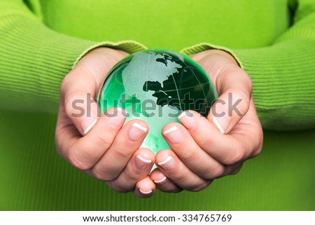 Environmental protection concept with glass globe in hand - stock photo