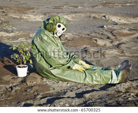 Environmental scientist and a plant in a pot, in the desert - stock photo