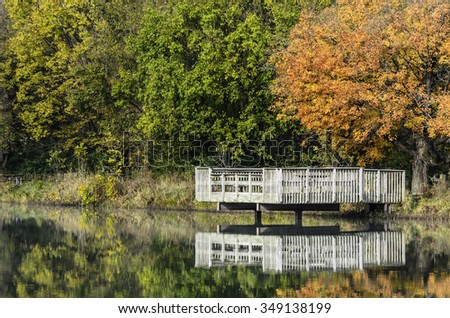 Environmental study in autumn: Wooden deck (for observation and fishing) over calm lake reflections by leafy woods in Silver Springs State Park, northern Illinois, USA, at the end of October - stock photo