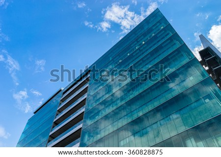 Environmental sustainable building with glass exterior, couds visible