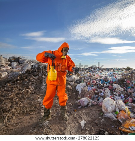 Environmentalist working on waste treatment on the landfill - stock photo