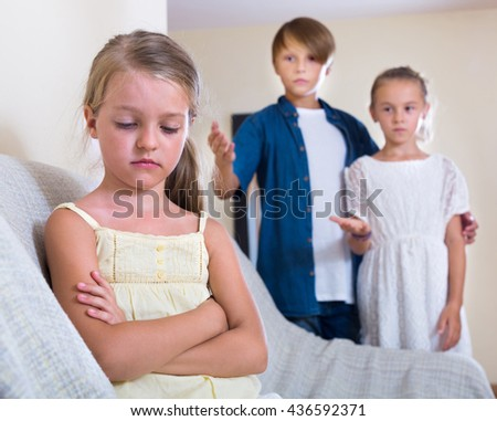 Envy child sitting aside of boy 11 years old and girl at home - stock photo