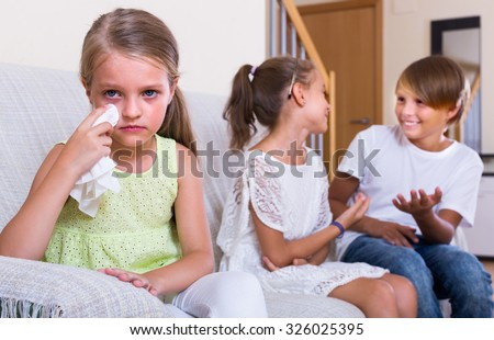 Envy child sitting aside of two children at home - stock photo