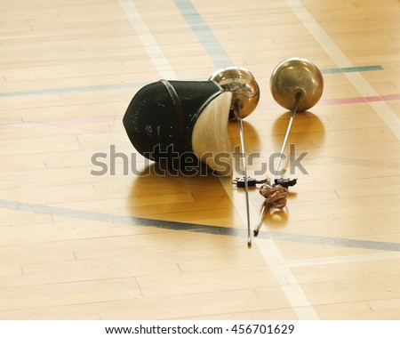 Epee swords and helmet for fencing - stock photo