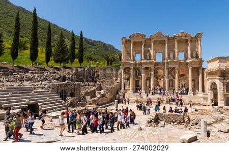 Ephesus, Turkey - April, 26, 2014: A group of tourists gather around a tour guide in the celsus library area of Ephesus in order to hear the guide tell them about the site - stock photo
