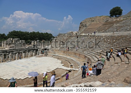 EPHESUS, TURKEY - AUGUST 10, 2015: Tourists in theatre in the ancient city of Ephesus, located in southwest Turkey. - stock photo