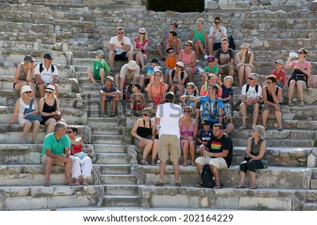 Ephesus, Turkey - June 25, 2014: A group of tourists gather around a tour guide in the celsus library area of Ephesus in order to hear the guide tell them about the site. - stock photo